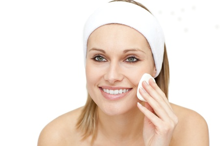 Cheerful woman putting make-up against a white background photo
