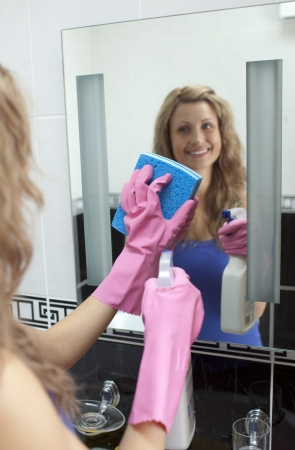 Smiling woman cleaning bathrooms mirror  photo