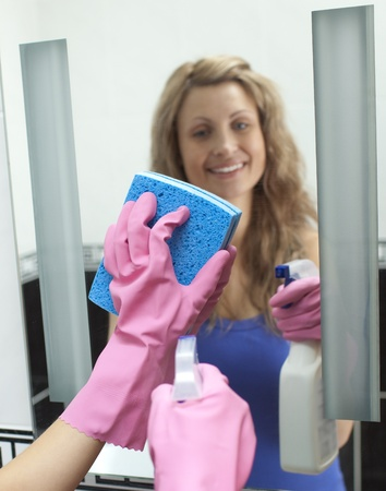 Cheerful woman cleaning bathrooms mirror photo