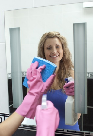 Attractive woman cleaning bathrooms mirror  photo