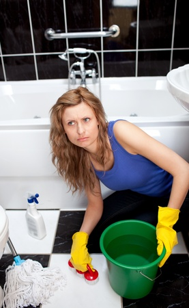 Unhappy woman cleaning bathrooms floor photo