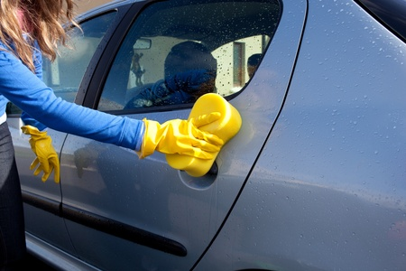 domestic garage: Close-up of a woman cleaning her car