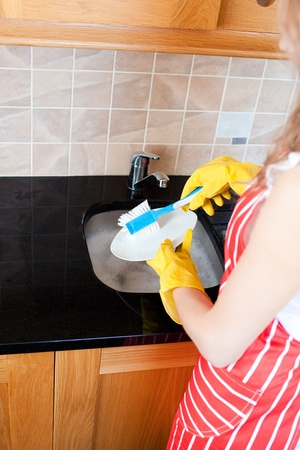 Close-up of a caucasian woman doing the dishes photo