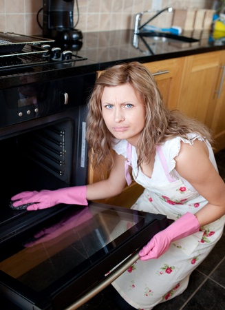 Annoyed woman cleaning the oven photo