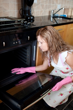 Tired woman cleaning the oven photo