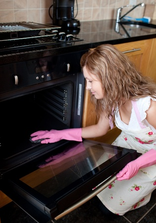 stereotypical housewife: Young woman cleaning the oven
