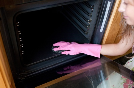special steel: Close-up of a woman cleaning the oven  Stock Photo