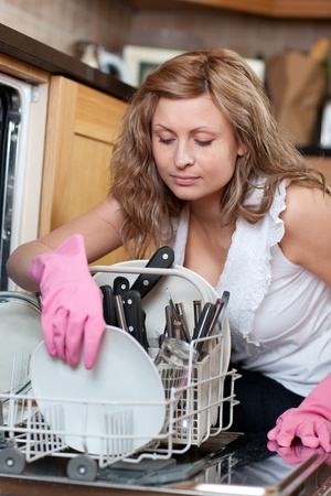 Young woman using a dishwasher  photo