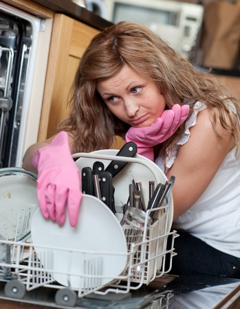 wash dishes: Tired young woman filing the dishwasher