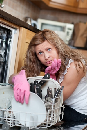 Tired blond woman filing the dishwasher  photo
