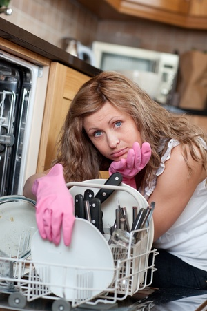 Tired cute woman filing the dishwasher photo