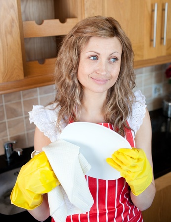 Smiling caucasian woman drying dishes  photo