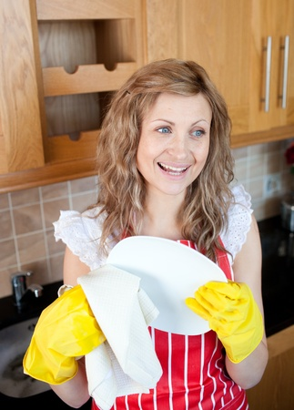dish washing gloves: Laughing blond woman drying dishes  Stock Photo