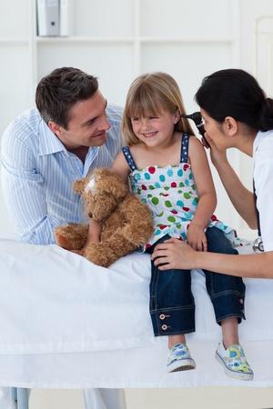 physical exam: Dottoressa controllando le orecchie della ragazza sorridente
