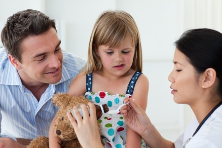 Serious female doctor giving medecne to a little girl Stock Photo - 10250378
