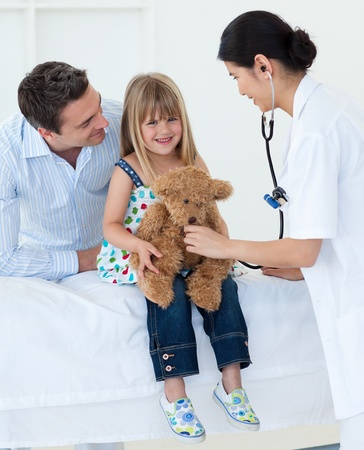 Female doctor and happy little girl examing a teddy bear photo