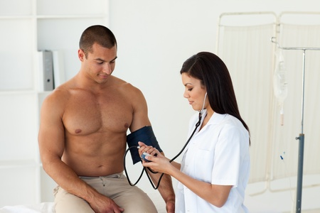 Confident female doctor checking the blood pressure of a patient photo