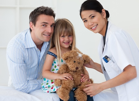Portrait of a doctor and happy little girl examing a teddy bear photo
