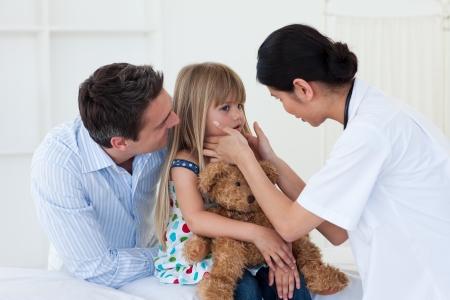 Female doctor examining little girl photo