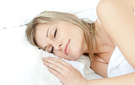 Radiant woman sleeping in a bed  photo