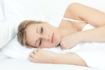 Bright woman relaxing in a bed photo