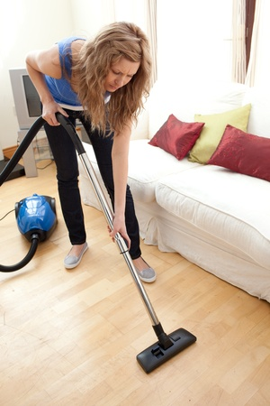 Portrait of a young woman vacuuming  photo