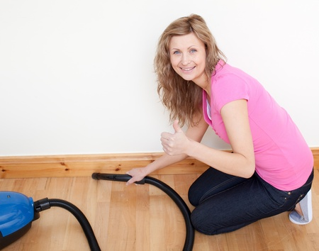 Portrait of a cheerful woman vacuuming