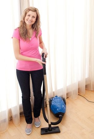 Portrait of a happy woman vacuuming photo