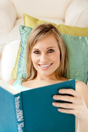 Charming woman reading a book lying on a sofa photo