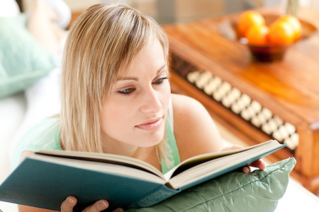 Serious woman reading a book lying on a sofa Stock Photo - 10248867