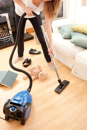 Young woman vacuuming the living-room photo