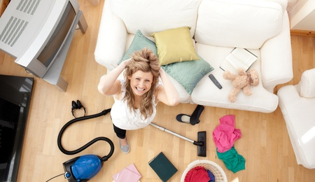 Frustrated blond woman vacuuming the living-room photo