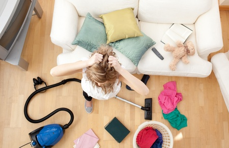Depressed blond woman vacuuming the living-room photo