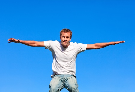 Cheerful man jumping against a blue background photo