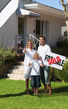 Smiling family with their new home Stock Photo - 10249062