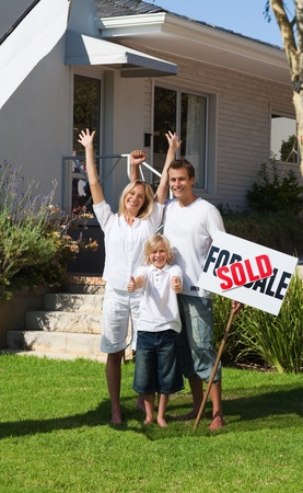 Smiling family with their new home in the garden Stock Photo - 10249048