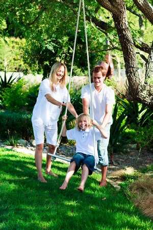 Happy familiy having fun swinging  photo