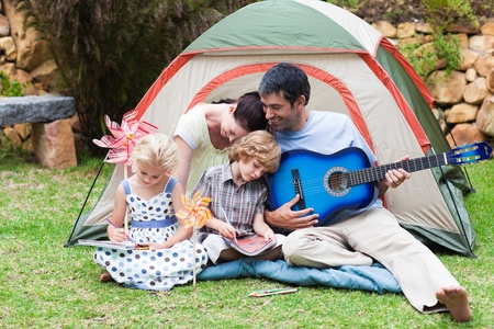Parents and children playing a guitar in a tent photo