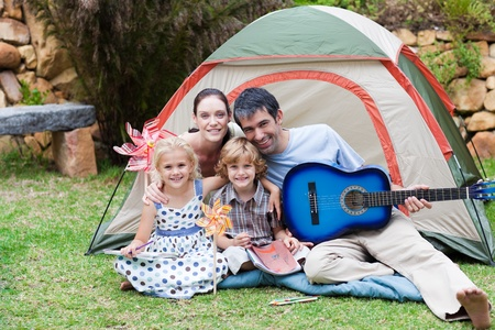 Family camping and playing a guitar photo