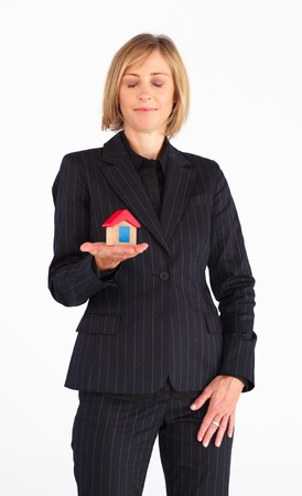 Confident businesswoman holding a house photo