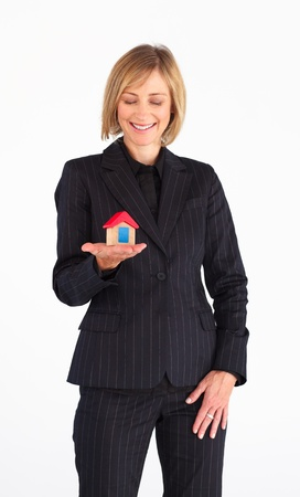 Friendly mature businesswoman holding a house in her hands photo