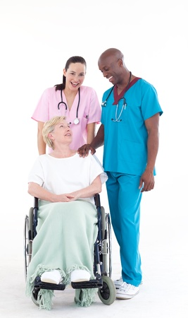 wheel chair: Nurse and doctor taking care of a senior patient in a wheel chair Stock Photo