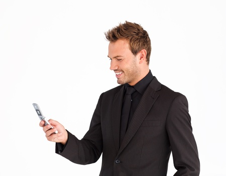 businessman phone: Smiling businessman writing a message with a mobile phone