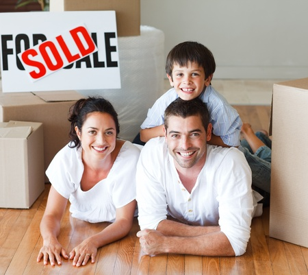 Family on the floor smiling at the camera after buying house photo