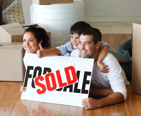 Happy family lying on the floor after buying house with thumbs up photo