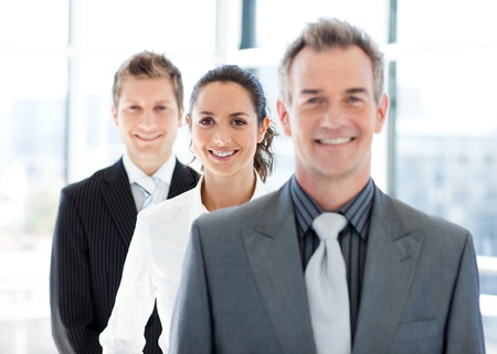 Smiling businesswoman in focus with her team photo