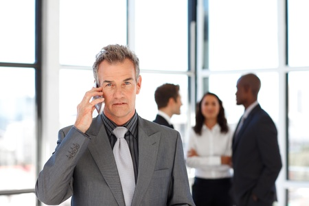 Mature businessman on phone looking at the camera photo