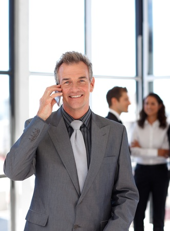 Smiling mature businessman on phone photo