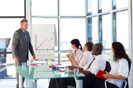 Senior businessman interacting with his team  photo