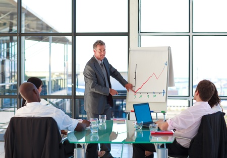 board room: Senior businessman reporting to graphs in a presentation